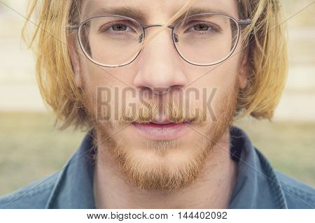 portrait of young bearded man with long red hair wearing glasses