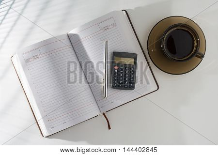 On The Table In An Open Diary And A Pen With A Calculator, Standing Next To A Cup Of Coffee.