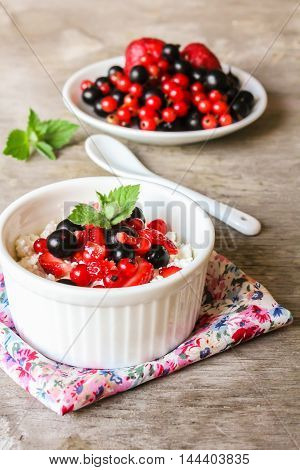 Homemade cottage cheese with sour cream, strawberry, red and black currant and fresh mint in a ramekin on a wooden table for breakfast, selective focus