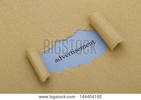 Advertisement word written under torn paper .