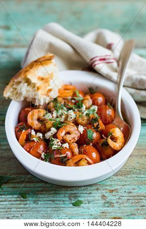 Traditional mediterranean dish with roasted cherry tomatoes, shrimps, salted greek feta cheese and fresh parsley in a bowl with homemade fresh bread on a wooden table, selective focus