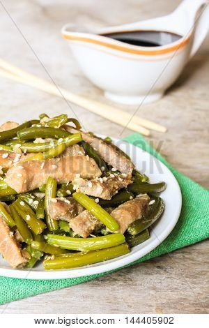 Traditional chinese dish with roasted pork, garlic, ginger and sesame seeds served with soy sauce, selective focus