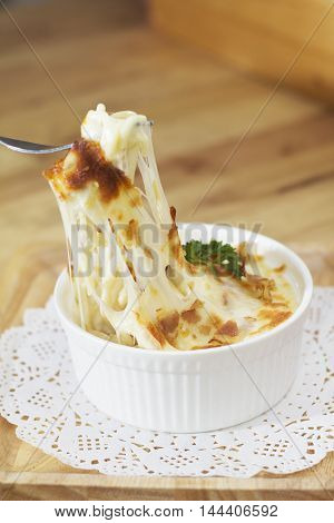 The spaghetti baked cheese on wooden background