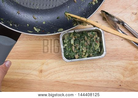Putting cooking spinach to box / cooking Baked spinach concept