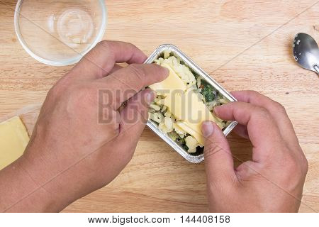 Putting cheese to spinach box / cooking Baked spinach concept