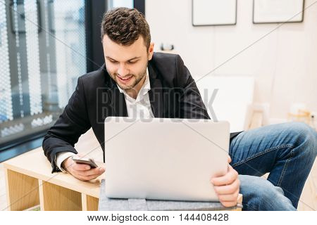 Young man working at a computer in the creative bright office gadgets business positive emotions business style