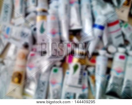 Colorful acrylic color tubes. Blurred abstract background.