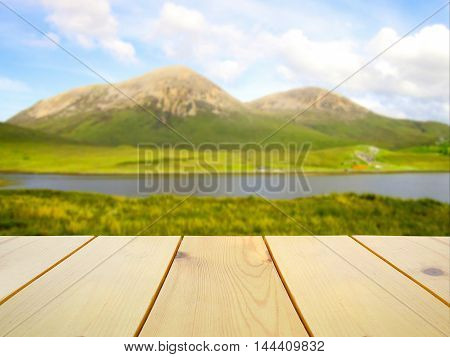 Wooden table on blurred stunning view of Isle of Skye Scotland background