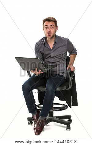 Tired manager, sitting on a chair with a laptop working. It shows positive emotion, holding the left hand on the chair, his right hand holding a laptop. Studio, white background.