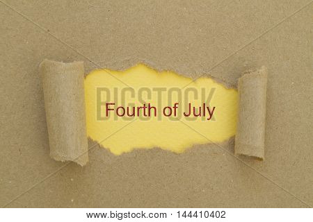 Fourth of july written under torn paper. Independence Day Fourth July concept.
