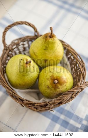 Pears with autumn leaves on wooden background