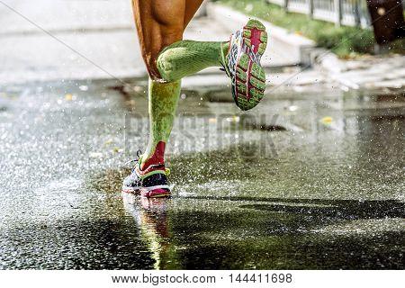 feet men runner compression socks running through a puddle water sprays