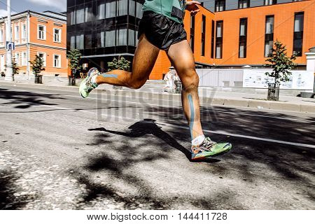 legs men marathon with taping on calf muscles running on a city street