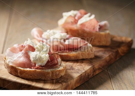simple ciabatta slices with speck and mozzarella on wood table
