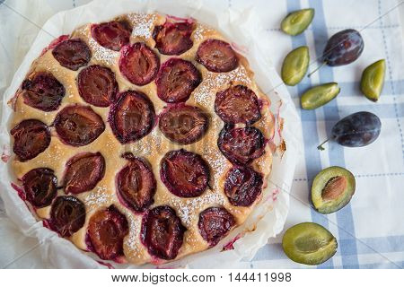 home made Plum cake over natural wood background