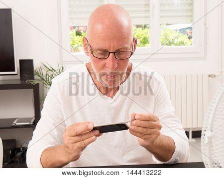 a mature man repaired a smart phone