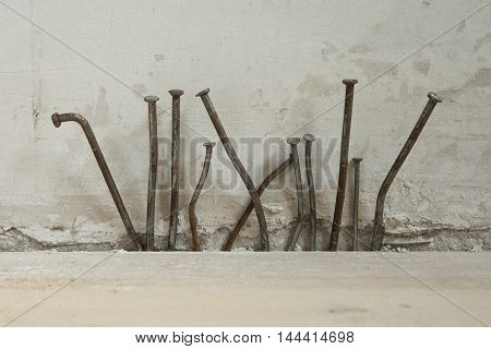 Composition of old crooked rusty nails in front of concrete wall. Home renovation work.