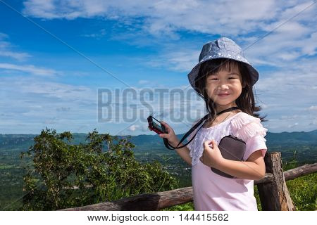 Happy asian girl smiling and looking at camera at national park . Child photographed views moutain againt blue sky with cloudy nature background. Child relaxing outdoors at the daytime travel on vacation.