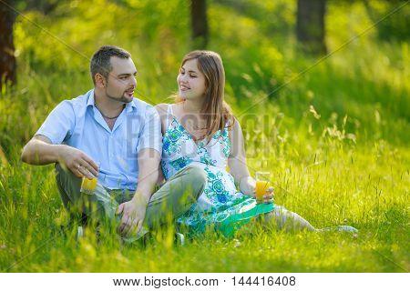 Happy pregnant couple drinking orange juice outdoors