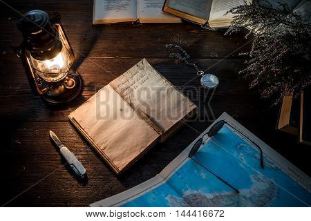 Old-fashioned kerosene lamp, map and accessories on the dark table in twilight.Soft focus