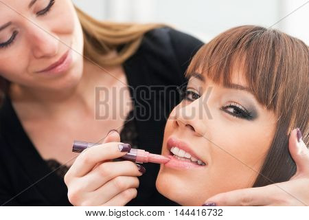 Makeup artist applying lip gloss, toned image