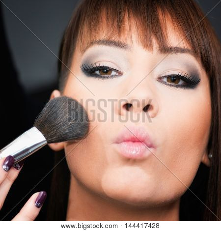 Professional make-up applying blush, toned image, square image,