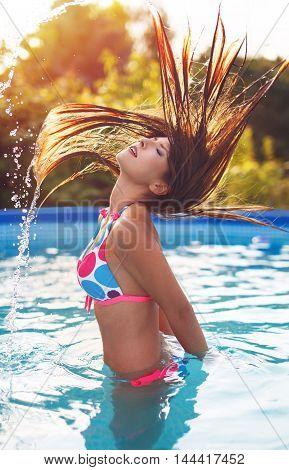 Woman splashing water with hair in pool sunset