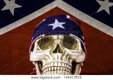 human skull with confederate head band in front of confederate flag