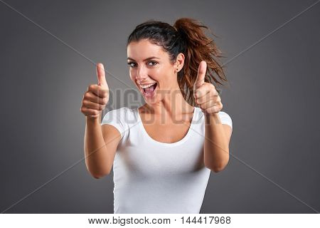 A beautiful young woman smiling and showing thumbs up.