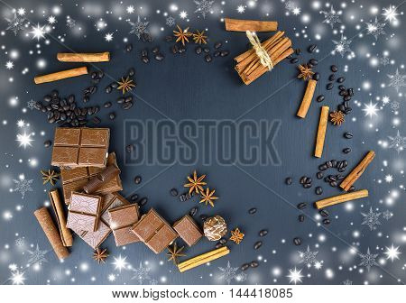 Beautiful Christmas background for a sweet tooth. Aromas and flavors of the holiday. Chocolate coffee beans cinnamon star anise / flowers / and candy on a dark background. Top view.