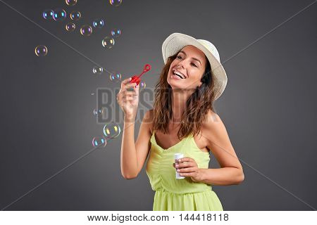 A beautiful young woman blowing soapbubbles in a green dress and a hat