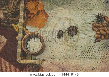 White perls with autumnal acorns and conesyellow leavescup with candy on the lace tablecloth.Vintage toned background.Selective Focus