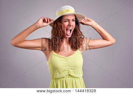 A beautiful young woman screaming in a green dress and a hat