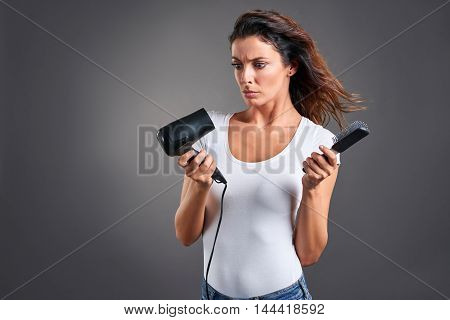 A beautiful young woman feeling frustrated and while holding a hairdryer and a hairbrush.