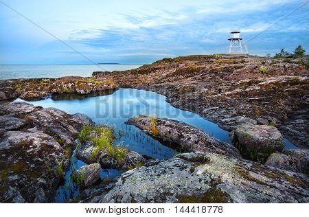 White lighthouse on rocky coast of the island