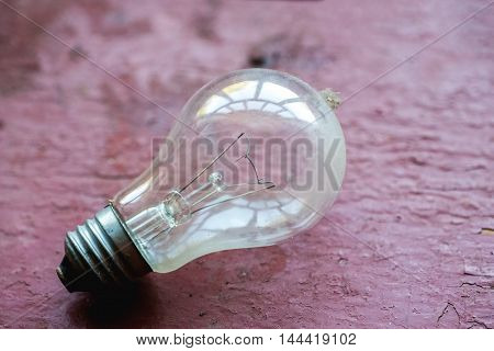 Dusty Light Bulb On A Red Table