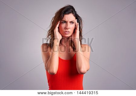 A beautiful young woman having a headache and grabbing her head in a red top