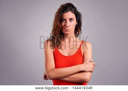 A beautiful young woman looking suspiciously and squeezing her mouth in a red top