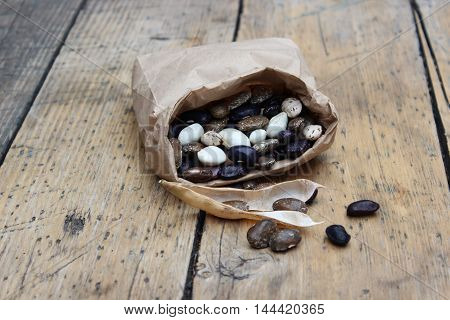 Large multi-colored bean in paper bag on background of boards