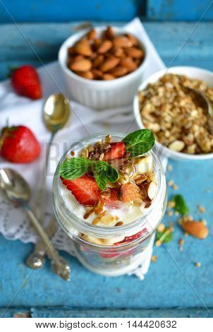 Oatmeal with yogurt kiwi banana strawberries and almonds in a jar of glass for breakfast