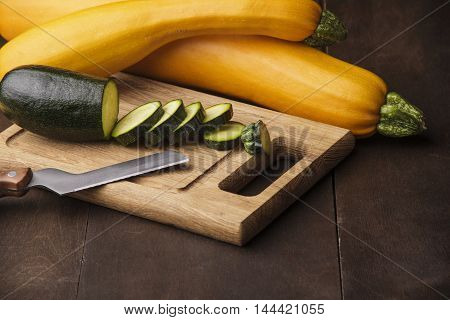 A fresh sliced zucchini on wooden kitchen desk with knife.wooden background.free space