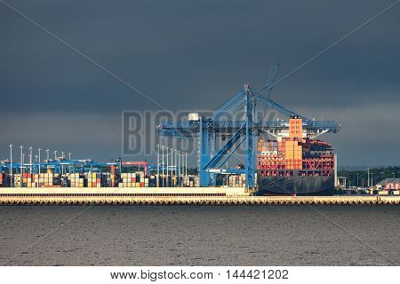 Stormy sea sky with container terminal in port.