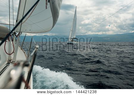 Yacht racing at sea in cloudy weather. Luxury boats. Sailing.