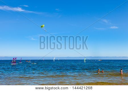 SOPOT, POLAND - AUGUST 24, 2016:  A tow boat is lifting a two people into the air to go parasailing above sea. Sopot beach very popular for water sport.