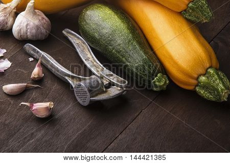 Garlic and galic crusher and three zuccini two yellow and green.Wooden background.free space