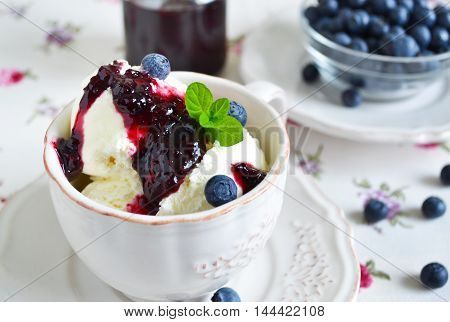 Vanilla ice cream with blueberry jam in a cup