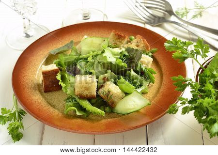 Fresh salad with lettuce green peas cucumber and croutons