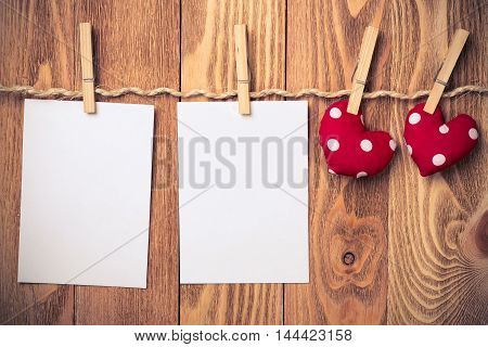 Blank sheets of paper with red handmade hearts pinned to rope on wooden background