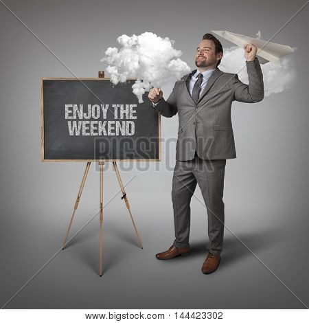 Enjoy the weekend text on blackboard with businessman and paper plane
