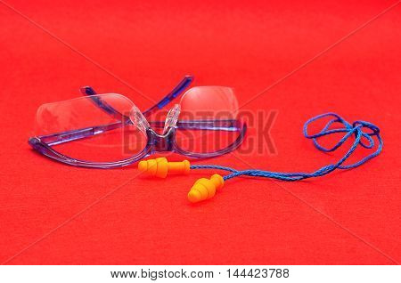 Safety goggles and ear plugs isolated on a red background